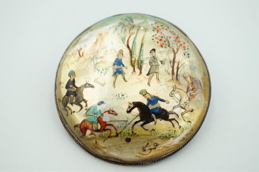 Broche en métal argenté sertie de nacre peinte d'une scène extrême-orientale de jeu de polo. Accidents. Poids brut : 17 gr.