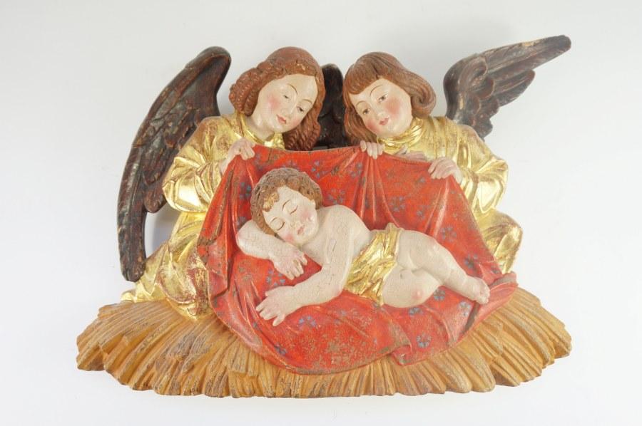 Bras reliquaire en bois sculpté, polychromé et doré reposant sur une base feuillagée à volutes.