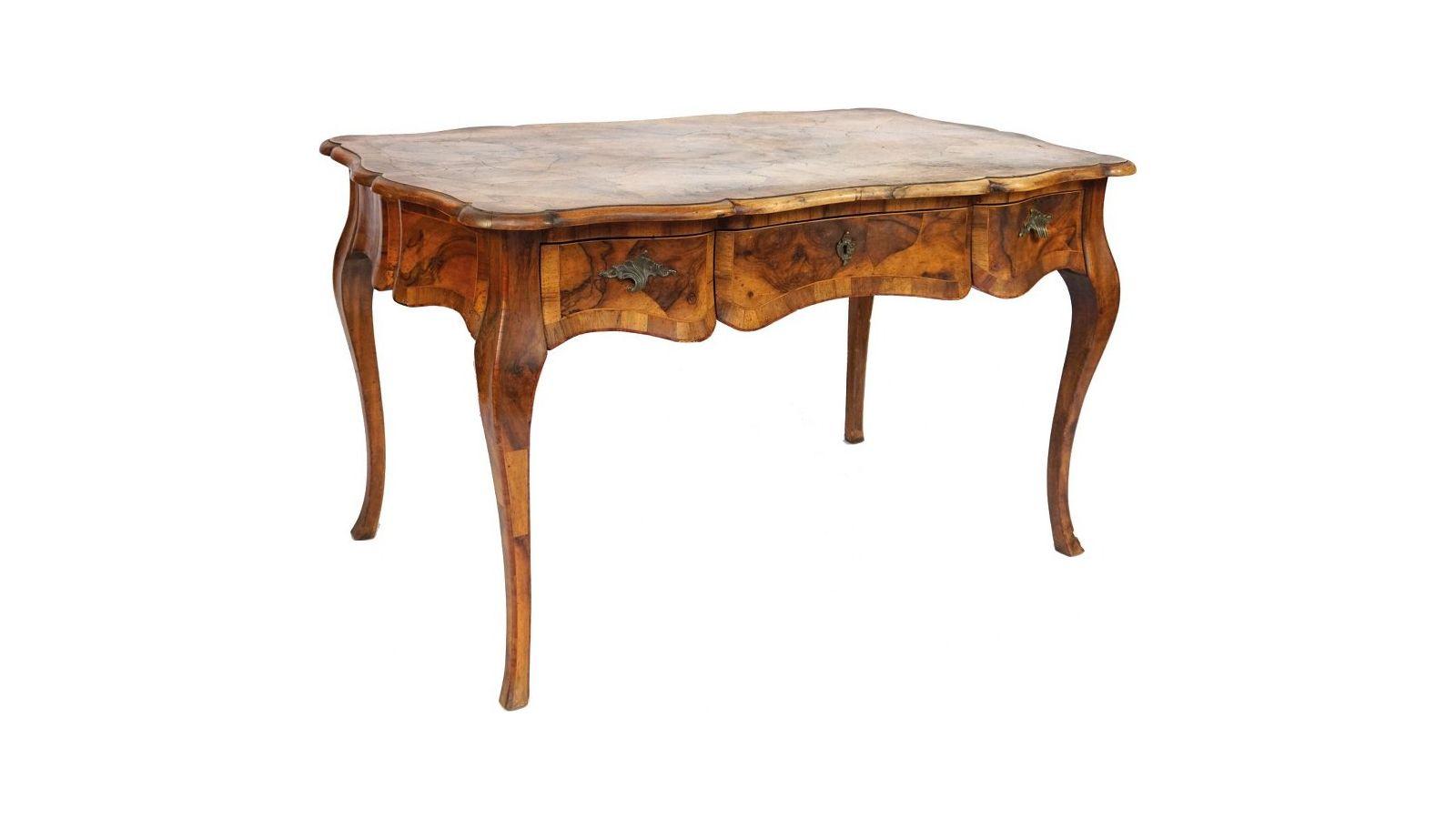 Bureau plat en marqueterie de bois de placage, de forme galbée, ouvrant à trois tiroirs en ceinture.