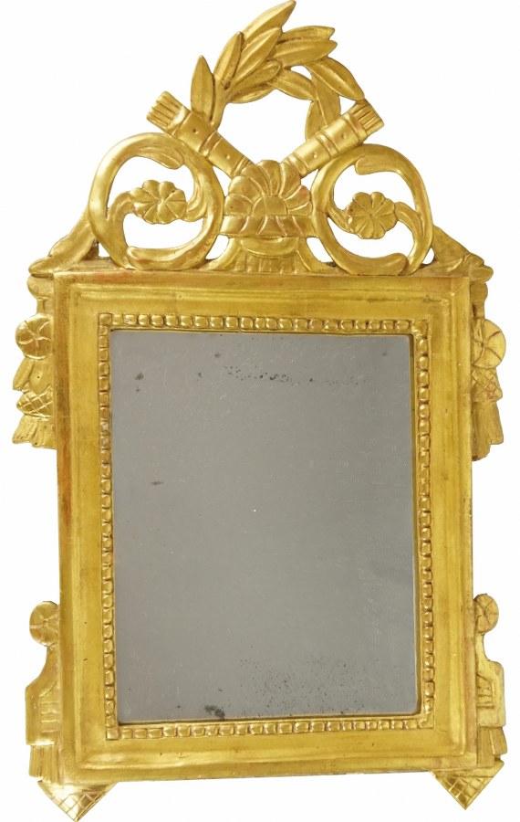 Miroir à fronton en bois sculpté, doré et rechampi gris à décor de guirlandes de laurier et frise de perles.