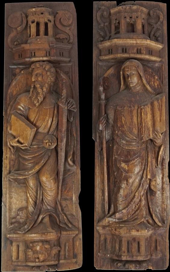 Paire de panneaux en chêne sculpté en haut relief représentant saint Paul tenant son épée et un livre ainsi qu'une sainte abbesse tenant un livre et une crosse.