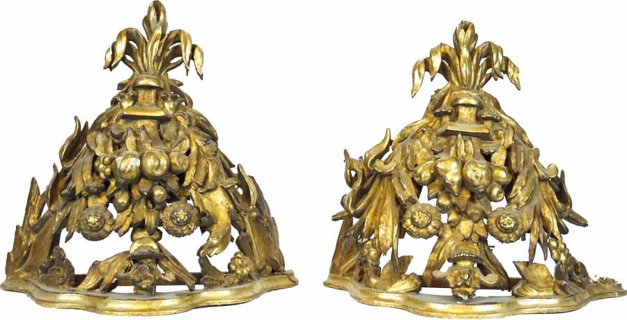 Paire de consoles en bois sculpté, ajouré et doré à décor de fruits et de fleurs.