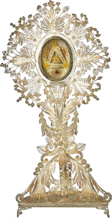 Reliquaire en métal blanc filigranné avec un ovale de paperoles.