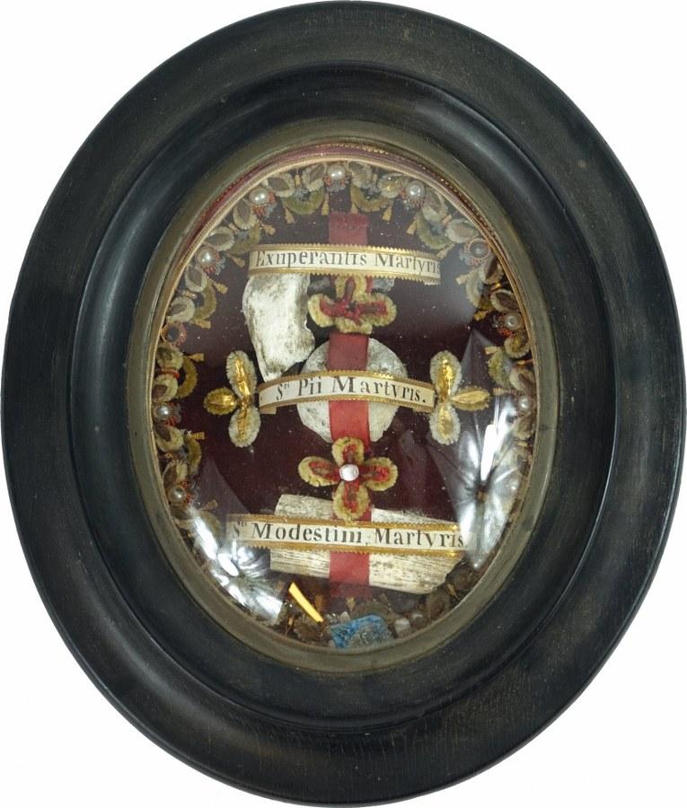 Reliquaire à paperolles de forme ovale sur fond velours annoté ' Exuperantis Martyris - Sti Pii Martyris - Sti Modestini Martyris'.