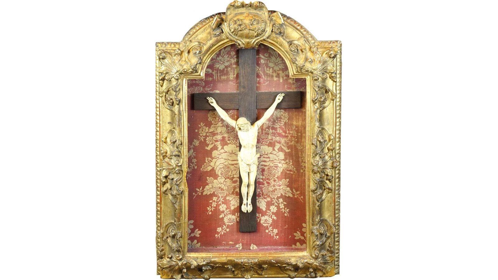 Christ  en ivoire, dans un bel encadrement en bois doré mouluré et sculpté de palmettes et cartouche centrale.