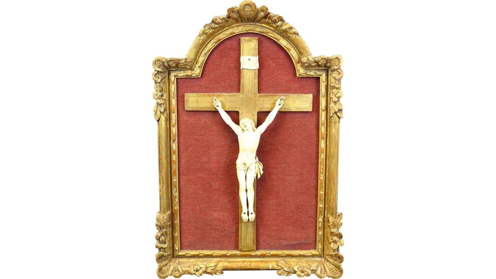 Christ en ivoire monté sur une croix doré, dans un encadrement doré.