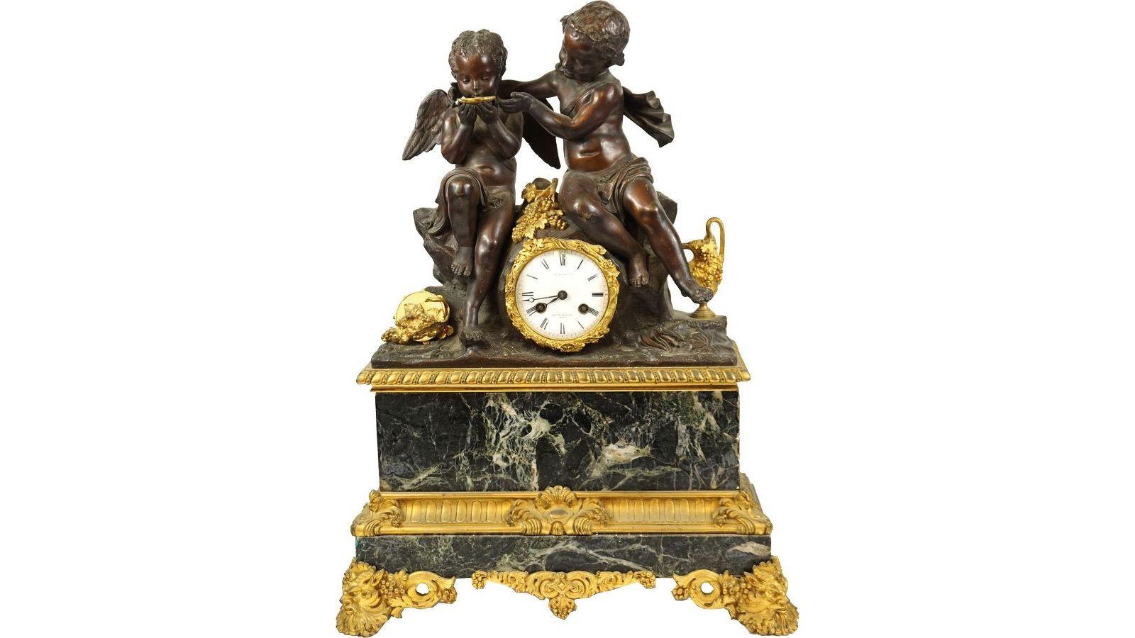 Pendule aux Putti, en marbre veiné et bronze à double patine dorée et brune nuancée.