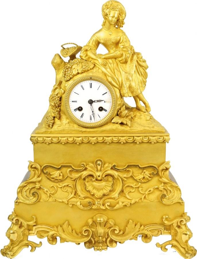 Pendule en bronze doré à décor en ronde-bosse d'une élégante au panier sur son socle en bois.